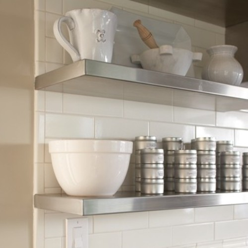 wooden floating shelves on white brick wall