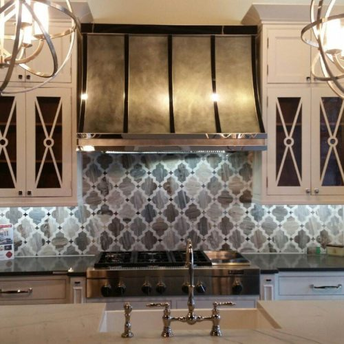 custom zinc and mirror rangehood above stove